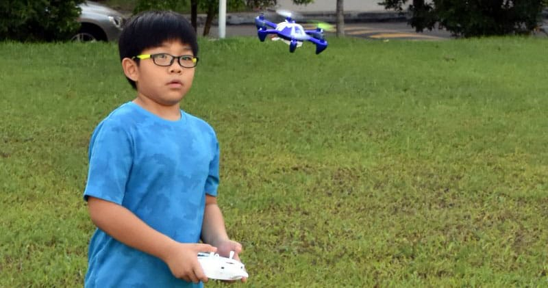 Young kid flying a drone in a park